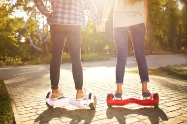 young man and woman riding on the Hoverboard in the park.  Skateboard Smart