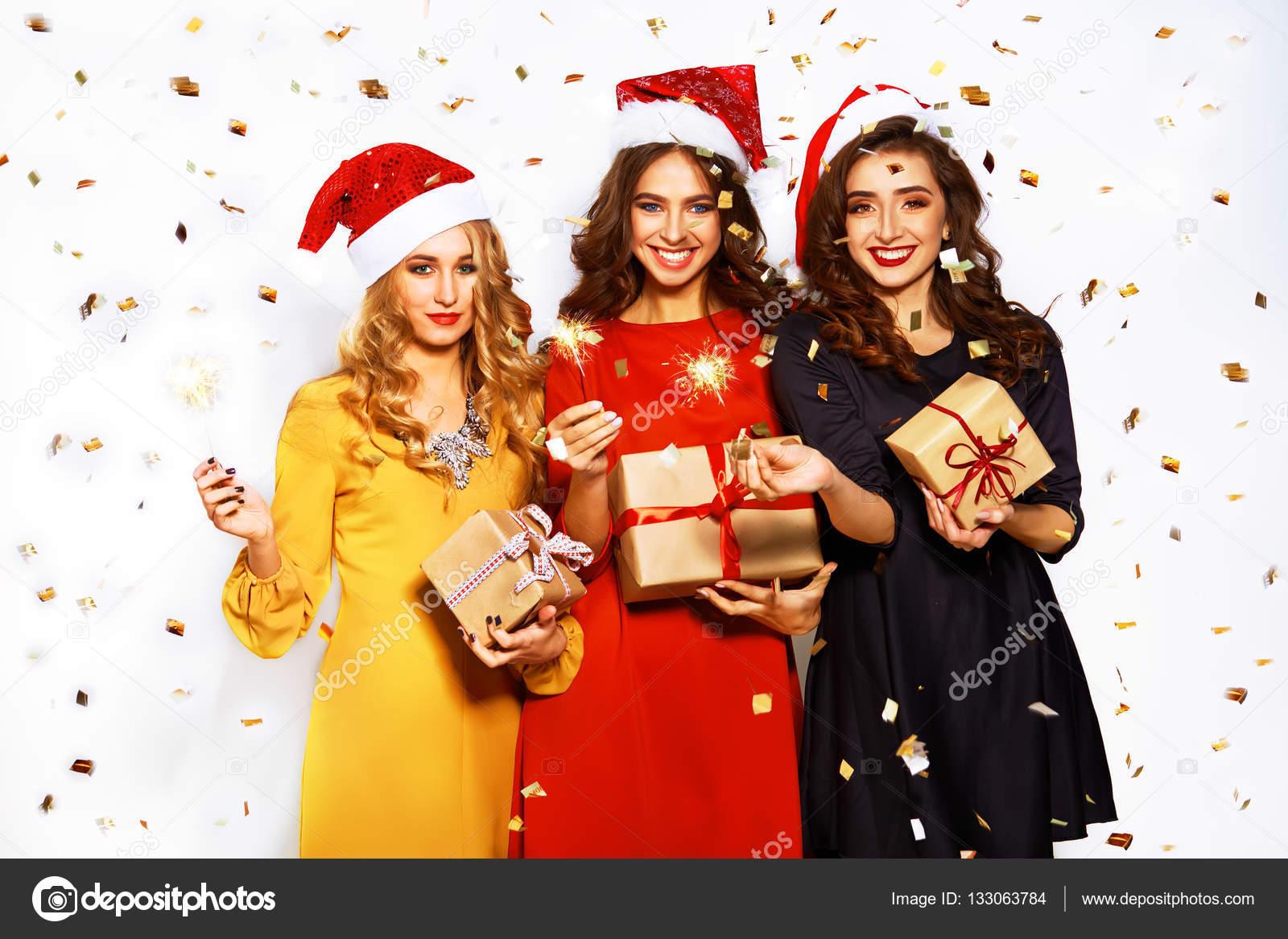 Retrato de tres mujeres jóvenes felices en sombrero de Papá Noel con  regalos y luces de f5ec9bf6b69