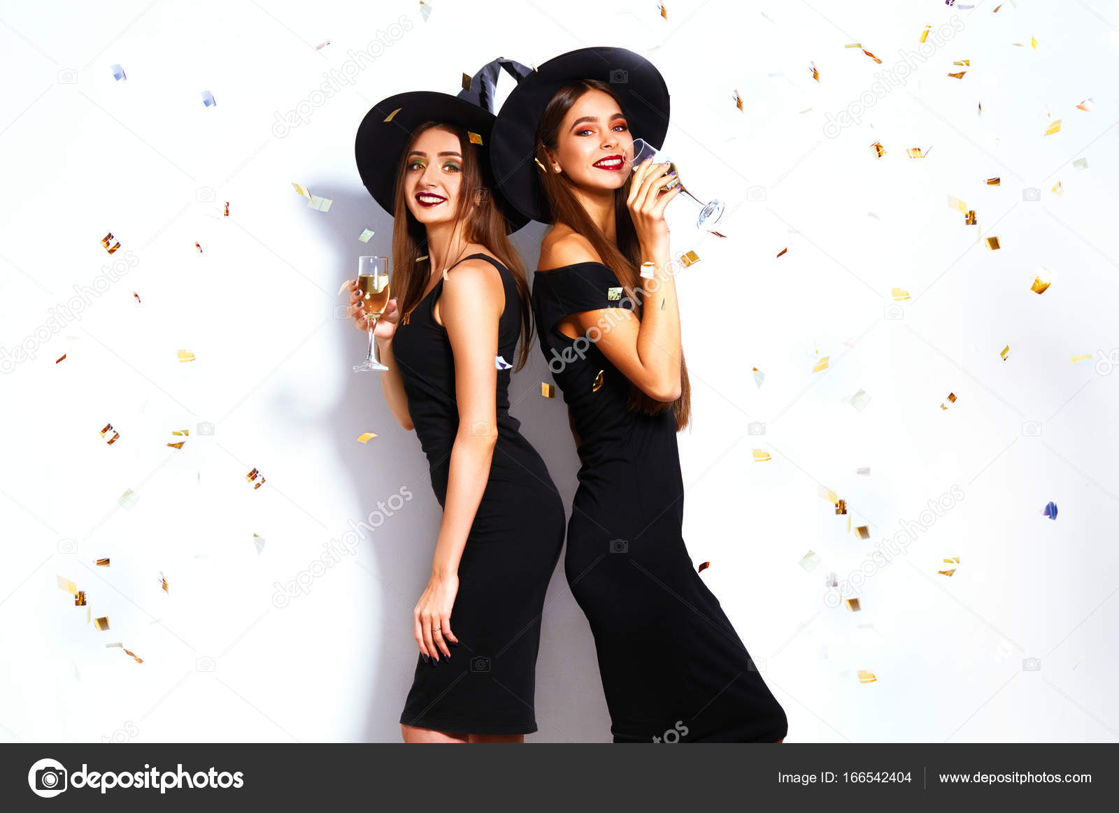portrait of two happy young women in black witch halloween costumes on party over white background