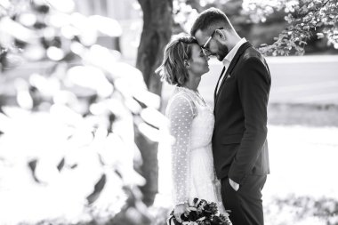 Beautiful black and white photo of bride and groom. Happy couple posing and smiling in wedding dress and suit with bridal bouquet in the park. People enjoy each other. Together. Wedding concept.