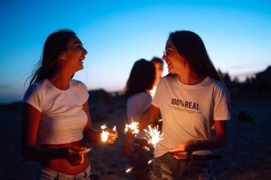 Geceleri plajda maytaplı bir grup arkadaş. Genç arkadaşlar plaj tatilinin tadını çıkarıyorlar. Yaz tatili, tatil, rahatlama ve yaşam tarzı konsepti.