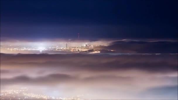 Měsíc na noční obloze nad městem. Nad městem plovoucí šedé mraky. Velký mrak viditelné města