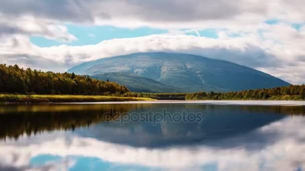 a Giant Mountain in Norway. Over the Hill Floating Big Gray Cloud. Through the Clouds Make Their Way Rays of Bright Sun.