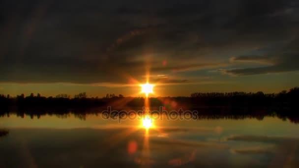 Krásný západ slunce. Slunce zapadá nad obzorem a na obloze ukazuje červenou. Plovoucí ve Sky tlusté šedé mraky, které jsou na obzoru červená