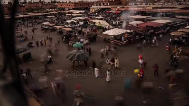 City of Morocco. Square with people and tents. Many people walk around the square.