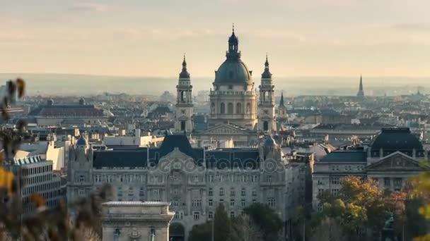 Budapest történelmi. Napsütés. Az égen fehér, sűrű felhők lebegnek. Növekvő zöldek, magas fák. A bazilika Szent Istvn épülete a Szent, a város jelképe