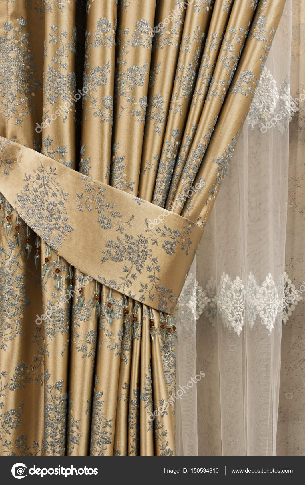 Partie du rideau magnifiquement drapé sur la fenêtre de la chambre ...