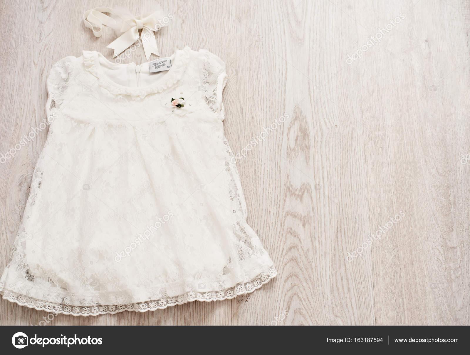 f3f137387 Vestido de renda branca do bebê vintage e Headband de laço em uma luz cinza  Wodden