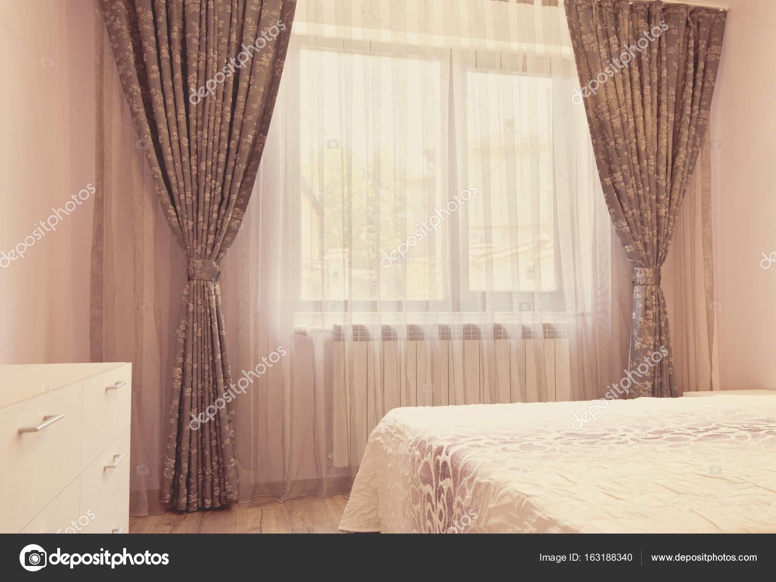 Lange donkere luxe gordijnen en gordijnen van tulle, rieten op een ...