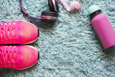 Pair of pink sport shoes, meter, water bottle and headphone over fur carpet. In the fitness room background. Accessories for running sport and exercise.
