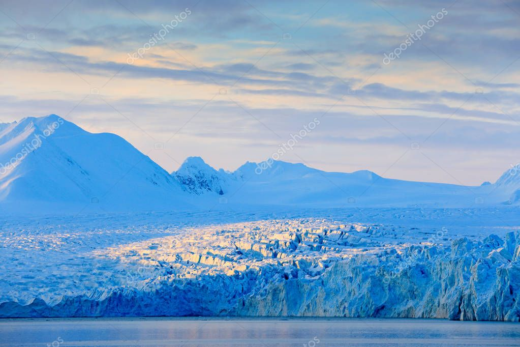 Land of ice. Travelling in Arctic Norway. White snowy mountain, blue glacier Svalbard, Norway. Ice in ocean. Iceberg in North pole. Blue sky with ice floe. Beautiful landscape. Cold sea  water.