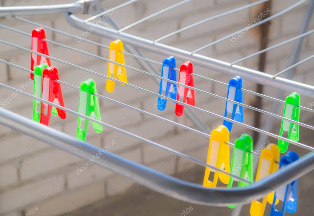 Multi-colored: red, yellow, green, blue clothespins on the clothes dryer