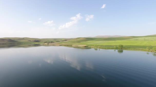 Kilátás a zöld rétek és a tó. kék ég és a természet. légi lövés drone 4k