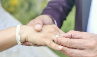 groom's hand putting a wedding ring on the bride's finger. Wedding ceremony.