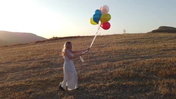 Šťastná veselá dívka s barevnými balónky běží přes louku při západu slunce na přírodě v létě. Zobrazení dronů 4k