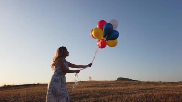 Šťastná veselá dívka s barevnými balónky běží přes louku při západu slunce na přírodě v létě. Zobrazení dronů 4k.
