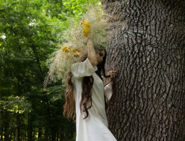 Young girl in wreath walks in forest. Folk style.
