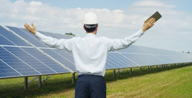 The technical expert rejoices the success in solar photovoltaic panels remote control performs routine actions to monitor the system using clean renewable energy Concept of remote support technology.