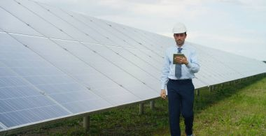 Engineer expert in solar energy photovoltaic panels with remote control performs routine actions for system monitoring using clean, renewable energy. concept applied to the remote support technology.