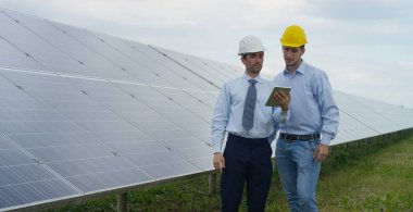 Two technical expert partners in solar photovoltaic panels, remote control performs routine operations to monitor the system using clean, renewable energy. The concept of remote support technology.