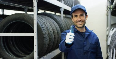 Specialist tire fitting in the car service, checks the tire and rubber tread for safety. Concept: repair of machines, fault diagnosis, repair specialist, technical maintenance and on-board computer.