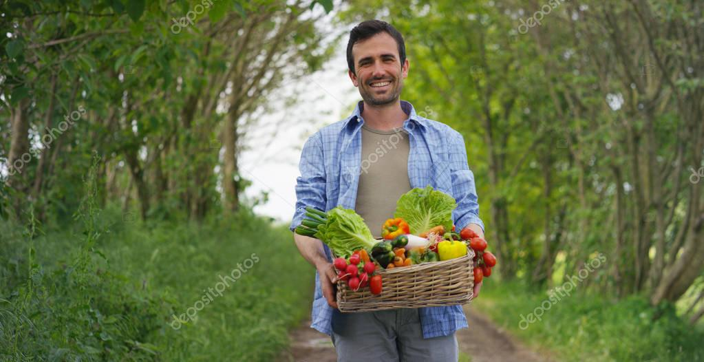 Portrait of a happy young farmer holding fresh vegetables in a basket. On a background of nature The concept of biological, bio products, bio ecology, grown by own hands, vegetarians, salads healthy
