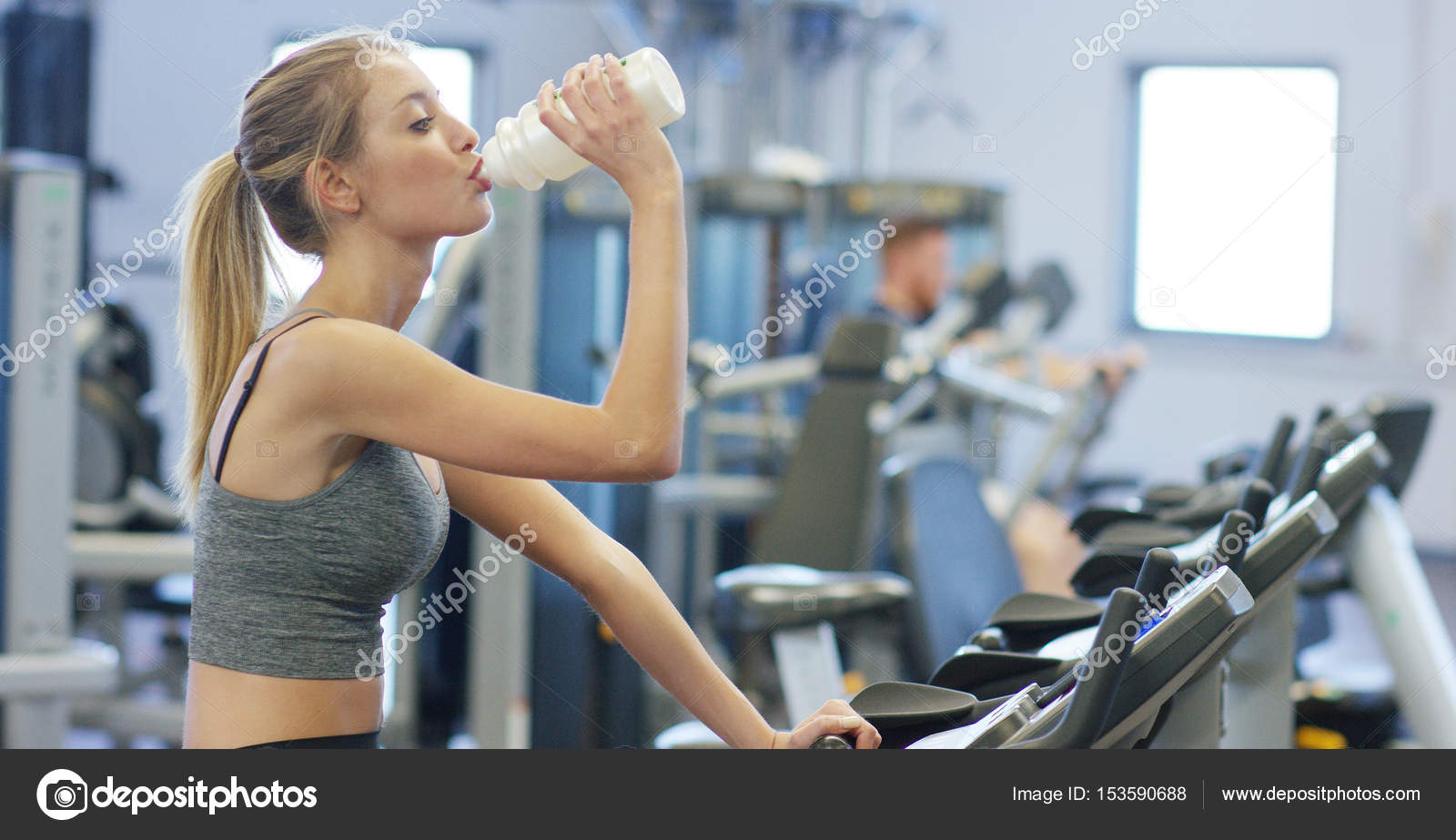 Young beautiful girl in a gym, shakes her legs on a cycling
