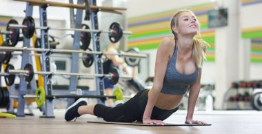 Young beautiful girl in the gym, doing stretching exercises for hands, feet and body, swapping all the joints. Concept: to love sports, to attend a gym, proper nutrition, a slender body, to be healthy