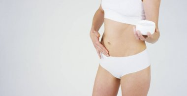 Young girl smears cream her beautiful, perfect body(waist), on a white background. Concept: vegetarian, diet, proper nutrition, spa procedures, fresh, fitness, bio products, body care, perfect skin.