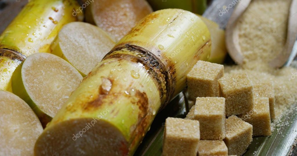 A macro shot of a composition of sugar cane, sugar cubes and sugar in the raw granules. Concept: a sweetener, nature, energy, juices and drinks.