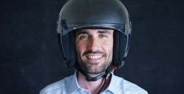 Portrait of a professional rider or motorcyclist, in a protective black helmet, on a black background. Concept: driver, drive, speed, protection, protective suit, reaction, love of extreme sports.