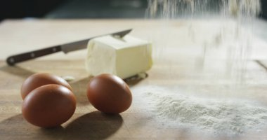 some flour fall down on wood table in extreme slow motion and nice composition with eggs and fresh butter