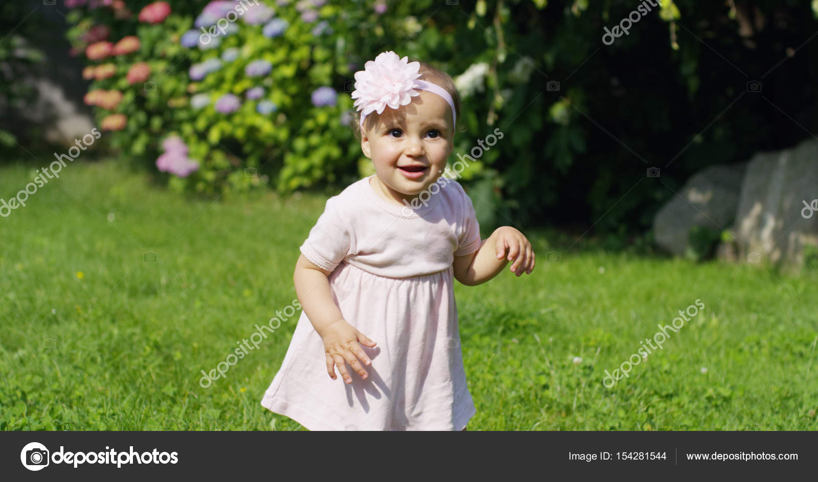 tender newborn baby girl trying to make the first steps in a garden