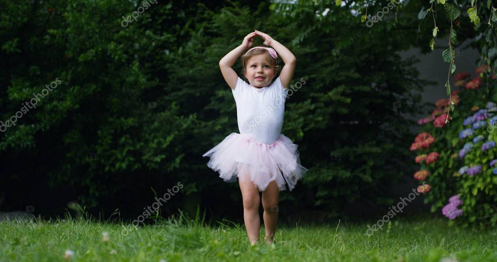little girl tries to take the first dancer steps in a garden dressed as a little dancer happy dancer funny . concept first steps and happy childhood nature . little funny children. cinema camera