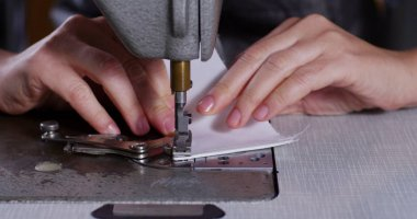 Slow motion sew of a hand of a young tailor who sew with a needle and thread by hand according to the ancient tradition of sewing.