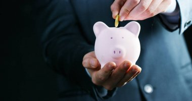 A man dressed in a suit and tie, puts money into the piggy bank. Concept: Pension, savings, investment, accumulation plan, savings for college studies.