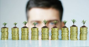 Businessman in a shoot macro above to hide the stack of coins in the seedlings. Concept: gains or income, investment banking, financing, and interest-free loans.