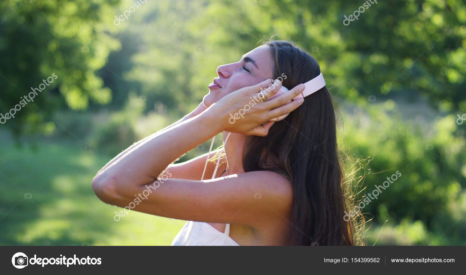 Een vrouw in het groen dragen koptelefoon luisteren naar muziek