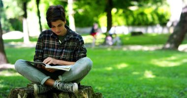 nice teenager 14 years old studying in the park in a sunny day and looking into the camera. healthcare and lifestyle concept.