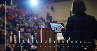 woman holds a speech to the audience in an futuristic and technology auditorium on a convention of economics and finance their business.concept:world economy,futuristic conference,holograms,technology
