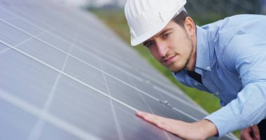 technical expert in solar energy photovoltaic panels, remote control performs routine actions for system monitoring using clean, renewable energy. concept applied to the remote support technology.