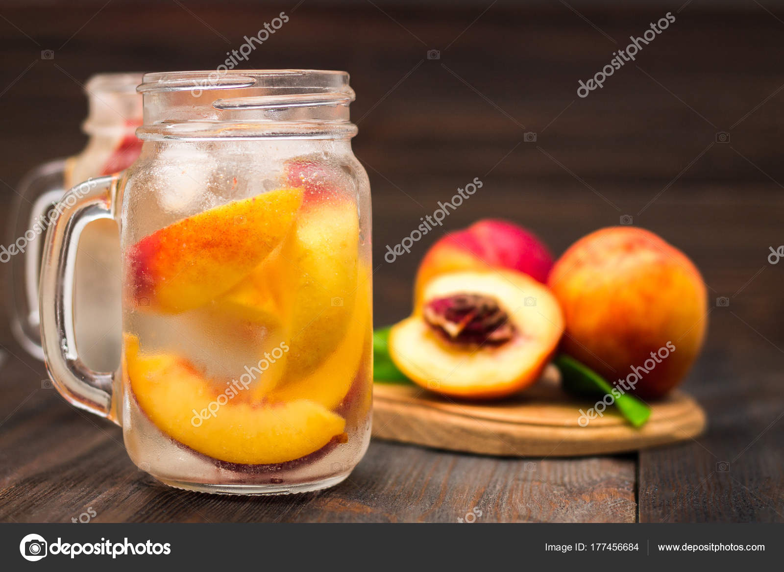 Mason Jar Glass Of Homemade Peach Iced Water On A Rustic Wooden Background Stock