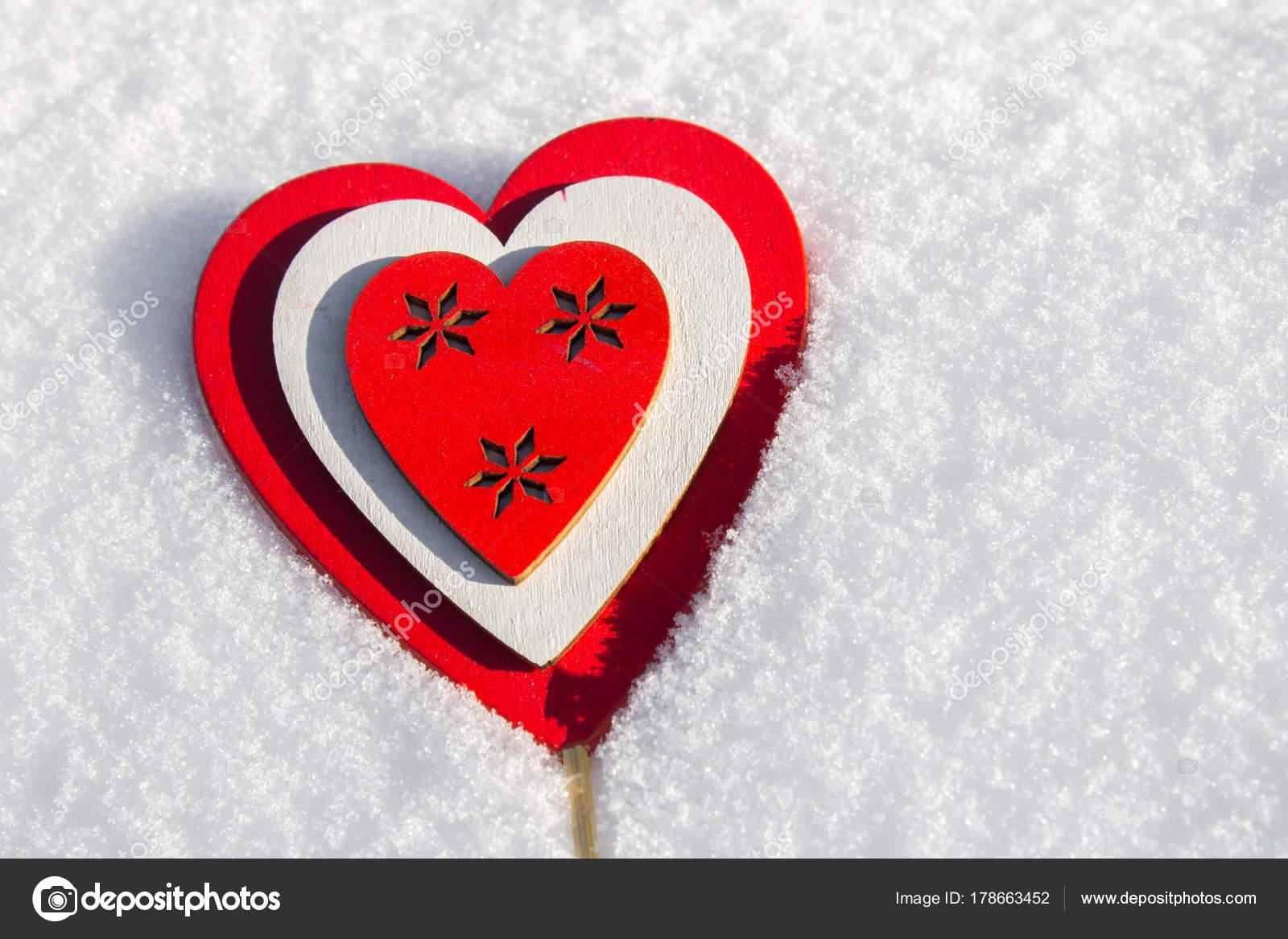 Im Schnee liegt ein rotes Herz aus Holz gemacht. Vorlage für eine ...