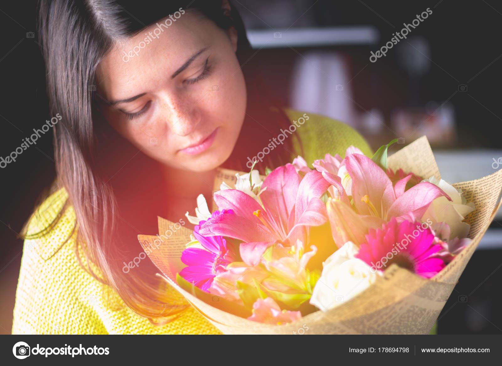 Hermosa chica con el pelo oscuro con un ramo de flores de un lirio ...