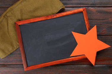 Chalkboard with empty space, military cap and red star on a wood