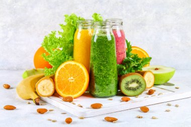Green, yellow, purple smoothies in currant bottles, parsley, app