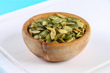Full bowl of pumpkin seeds close up on a wooden table.