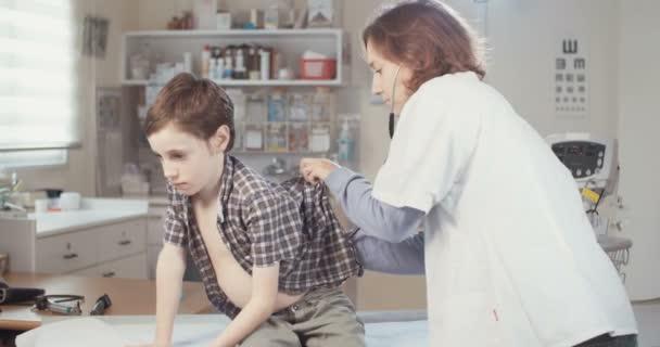 lékař provádějící prohlídku na mladého chlapce