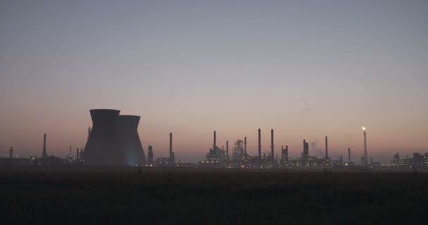 Large oil refinery silhouette against the sunrise.