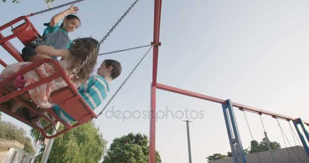 happy children swinging on swing